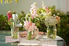 Using different sized mason jars with flowers for centerpieces