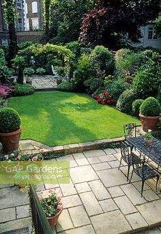 Small formal town garden with paved patio, dining table and chairs, lawn, containers, borders and arch dividing separate patio at far end of garden � London #formalgardens