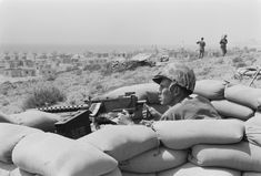 U.S. Marine sits in a foxhole and points a machine gun towards Beirut, Lebanon, in the distance