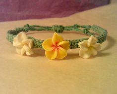 This handmade bracelet is made from dyed sky blue hemp, with two small white and one small yellow polymer plumeria beads. Each plumeria bead