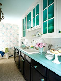 What a color scheme! Pastel teal paint on ceiling and inside cupboards and teal glass knobs; black base cabinets on bottom & white-glass-fronted cabinets on top.  Add the b-board & teal tile full backsplash, and the painted rug floor path and enjoy.