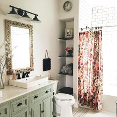 Anthro style bathroom. Love the sage cabinets and dark flower curtain