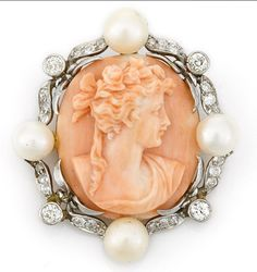 A coral cameo, cultured pearl and diamond pendant/brooch, circa 1890 cultured pearls measuring approximately 7.8 to 6.8mm; mounted in platinum-topped fourteen karat gold