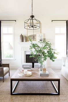 Modern wood and metal coffee table, greenery centerpiece in milk jug, iron light fixture, white couch.
