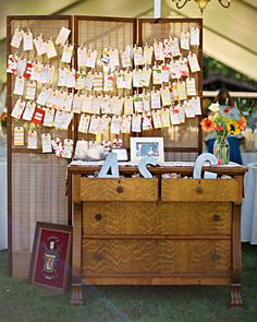 Escort cards are pinned to a screen at the entrance to the reception tent. The dresser holds metal letters -- one for Alivia, one for Scott, and one for their new shared last name, Gibbens.