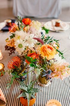 a hodgepodge of flowers, photo by Sweet Little Photographs http://ruffledblog.com/modern-palm-springs-wedding #weddingflowers #orange #centerpieces