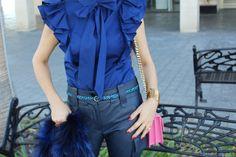 Camisa de volante en azul si mangas , cinturón animal print , pantalones en azul , y bolso  en rosa