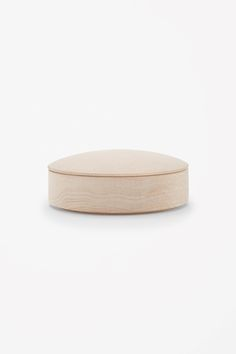 Inspired by the shape of projector lenses, this storage box has a curved lid and is made from smooth maple wood.
