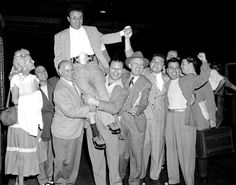 Raging Bull.  Middleweight champion Jake LaMotta finds himself hoisted on the shoulders of his admirers as he arrives at Grand Central Station in 1950. The boxing pro was joined by his proud wife Vicki (l.) and his brother Joe, who trained him (far right).