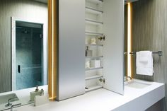 Flush-mounted cabinetry creates a look of seamlessness in the master bathroom. Here is the medicine cabinet!