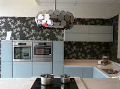 Love the pale blue cabinets & monochrome wallpaper in this kitchen. The Vintage cooker hood from BEST looks great!