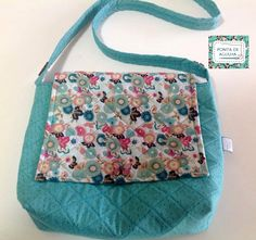 Bolsa colorida, confeccionada com tecidos nacionais e importado e quil reto. Possui bolso interno e botões decorativos. <br>Peça única.