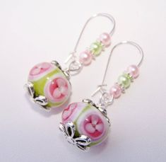 Gorgeous green, pink, and white lampworked beads with gorgeous flower bead caps have been strung from kidney earwires which are beaded with coordinating green and pink glass pearls. The lampworked beads are about 22mm and the glass pearls are 4mm. The earrings hand 1 3/4.