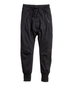 Black. Sweatpants with dropped gusset and tapered legs. Elasticized drawstring waistband, side pockets with zip, and one back pocket. Ribbed cuffs.