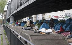 Hundreds of migrants, mostly from eastern Africa, living in tents under a subway bridge in Paris