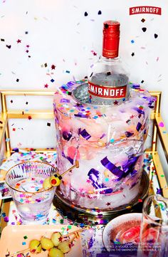 This cute New Year's Eve party hack will keep your Smirnoff chill till midnight. Just 3 easy steps and viola! Confetti Glitter Ice Mold!   SIMPLE INSTRUCTIONS Step 1: Cut the top-half off of a two liter soda bottle.   Step 2: Fill the soda bottle with water + place the Smirnoff No. 21 Vodka inside.   Step 3: Fill the water with confetti and glitter.   Step 4: Freeze overnight. Remove just before your guests arrive.   Now pass the chilled drinks and enjoy the best year yet.