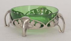 Archibald Knox - Liberty & Co - A polished pewter and green glass small dish