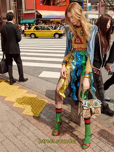On the streets of Tokyo, an image from the Gucci Fall Winter 16 campaign. A gold intarsia long sleeve crew neck top and tulle skirt with allover sequin embroidery, the knot sandal and appliquéd Gucci Dionysus shoulder bag.