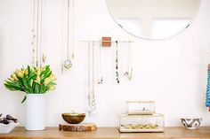 Wooden bedroom dresser, white walls, circular mirror, white flower vase, glass boxes, and wooden and brass jewelry storage