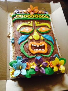 Tiki cake. Vanilla sheet cake with a layer of strawberry buttercream. Covered in a whipped chocolate frosting spread to look like carved wood. Fondant face, gumpaste flowers. Brown sugar sand around the edge