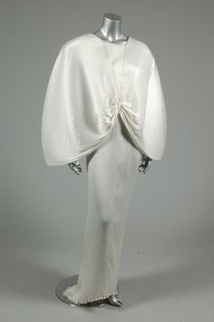 Yuki white pleated satin evening gown, Autumn-Winter, 1984, with central V-shaped top stitched bodice panel bordered by cape-like pleated satin wings convegring at the centre waist, extremely low scooped back, over columnar skirt