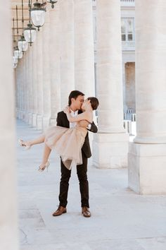 Groom holding bride in his hands by the columns at Palais Royal pre-wedding portrait captured by Paris Photographer Federico Guendel