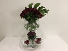 Red roses in fish bowl with monstera leaf