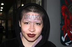 WTF? Not contempt with looking weird with shaved eye brows, she decides to have her favourite R'n'B star's name tattooed on her forehead.