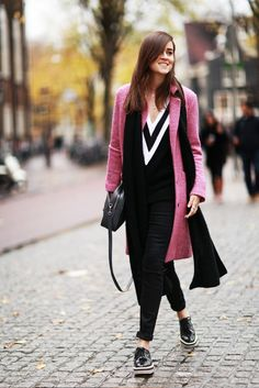 A v-neck sweater is paired with a pink coat, black cuffed jeans, platform oxfords, and a black scarf and bag
