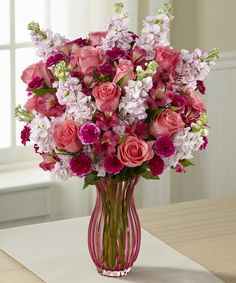 Timeless Elegance Bouquet - A mother's love is timeless, and so is this stunning bouquet of coral roses, pink stock, fuchsia mini carnations and dark pink alstroemeria gathered together in a curvy coral glass vase.