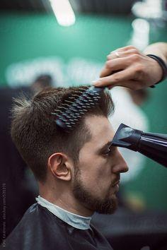 Barber blows hair dry during haircut at Barber Shop