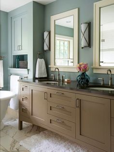 Taupe + Dusty Blue + Off-White-Muted blue walls surround this bathroom with calming energy. The vanity was given a fresh coat of sandy-brown paint, which echoes the muted hue of the bathroom's walls. Warm off-white furnishings, such as the marble floor and the painted mirror frames, blend well into the room's relaxing aesthetic