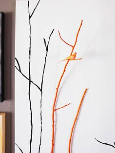 Twiggy Canvas     Using black acrylic paint and a thin paintbrush, paint several vertical twigs and birds on a stretched canvas. Find a real twig that roughly matches the size of your hand-painted ones, then paint it with a bright color (we chose fiery orange). Hot-glue a bird, painted the same color, to the twig, then hot-glue the twig to the canvas.