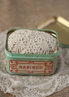 pin cushion in a vintage tin with a doily on top. good idea.