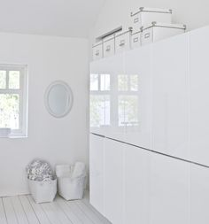 Great laundry room storage. Like the old wooden floors painted white. White ikea besta shelf unit cabinets with doors in high gloss white.