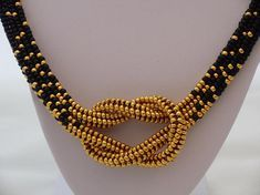 Elegant Chain Hercules knot made of matt Black and golden seed beads. The chain consists of two strands, which are pushed into each other, resulting in the knot effect. The total length with closure is approx. 55.5 cm. Design by Puca