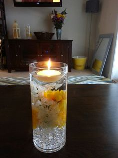 Floating candle centerpiece....made with glass cylinder, decorative diamond cut stones found at GardenRidge, artificial flowers, and a floating candle....