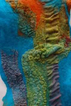 This scarf is hand-felted using highest quality merino top in shades of Pumpkin and Aqua blue. Nuno felted into the wool are torn strips of various sizes, shapes and fabric: tulle, hand-painted silk, merino pre-felts.