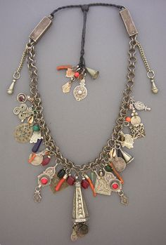 by Moroccan Designer Fouzi |  A true treasure necklace from the depths of Morocco, composed of earrings from the High Atlas Mountains, a Foulet hamsa from Ouarzazatte, a citadel pendant, hamsas, bohemian glass beads, coral and coin pendants, coral and anti-Atlas pendants, a perfume amulet from Ait Baha, a foum zguid hair ornamental cone from the Tata Province, a spiral of life hamsa, a High Atlas pendant and an Essaourian pendant. All on a silver chain. | 3'250$