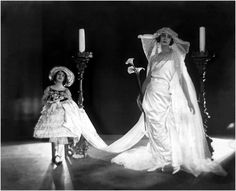 Model Helen Lyons wearing a pearl-embroidered, white satin and antique lace wedding dress by Gidding with Nadia Gary, as flower girl. Image by Baron Adolphe De Meyer,1921 © Condé Nast Archive/Corbis