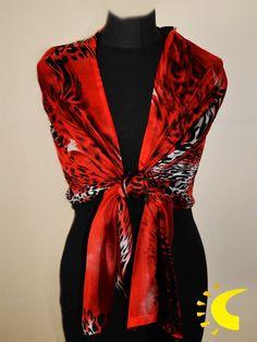 Chal de Seda con doble tejido, por un lado de color negro y del otro  en estampado con print animal con fondo rojo. Es un complemento muy vistoso, atrevido y elegante que realzará tu atuendo de ceremonia.  Se puede usar como fular en un evento casual. Es también un regalo muy distinguido.  Composición: 100% seda.  Medidas: 180 x 55 cm.  Cómo usar: Este chal de seda combina con una ropa de color negro, rojo o gris.