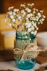 blue mason jars filled with baby's breath and wrapped with burlap