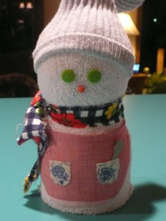 """These snowmen are made of tube socks stuffed with plastic shopping bags. Put a canning lid in the bottom of the sock. Stuff the bags in and then tie off the top of the white sock with string or yarn. Take a different color sock, cut the foot part off and discard. Tie the ankle closed with yarn, invert a bit to hide the cut edge, and tie again. Slip this """"toboggan"""" over the tied end of the white sock. Cut some fabric long enough to make a scarf and tie that around to make the neck. Hot…"""