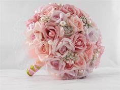 **ESTE BUQUÊ É ACOMPANHADO DO BOUTONNIÈRE.  Este buquê pode ser feito nas cores vermelho, rosa chá, rosa intermediário, rosa claro, lilás claro, lilás escuro,branco, amarelo, salmão, laranja e marfim.   Acompanha caixa apropriada para conservação e transporte no dia do evento  :: Apresentação  Buquê composto por flores, broches e pedrarias. Flores compostas por Ethil Vinil Acetat em tons de rosa e lilás suaves. Inclui pérolas em sua composição, além de broches prateados compostos por pérolas…