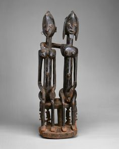 Seated Couple, 18th–early 19th century. Dogon peoples. The Metropolitan Museum of Art, New York. Gift of Lester Wunderman, 1977 (1977.394.15)   The figures' elongated bodies are depicted as a series of parallel vertical lines traversed by horizontals that draw them together. With understated elegance and an economy of detail, the artist distilled man and woman to a perfectly integrated and harmonious union. #OneMetManyWorlds