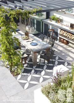 """Välplanerad yta för både matlagning och middagar. Ytan är fint markerad med en """"matta"""" av mönstrade plattor och kommer i sinom tid att få ett grönt tak."""