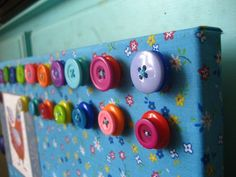 Spontan magnetic board covered in fabric (with Mod Podge) and magnets with hot glued buttons on them