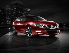 2016 Nissan Maxima shown in Coulis Red, side view in front of a night time skyline