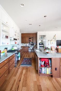 Open concept kitchen, white and wood cabinets, sea glass subway tile backsplash