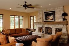 Warm brown and neutral tones create a cozy welcome in this living room. A large stone fireplace with a sturdy wood mantel brings warmth to the space, while above, a ceiling fan keeps it cool during the warmer days.